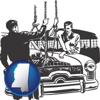 mississippi auto mechanics hoisting an engine out of a car with chains